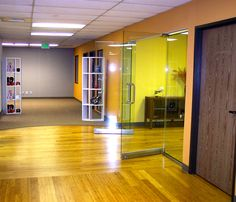 Corporate office space remodel from Space Case Design. Design features a bamboo floor which changes direction, leading the eye into the conference room. A frameless glass opening creates a spacious feeling with lots of light --a design for productivity. By Space Case Design, Redondo Beach.