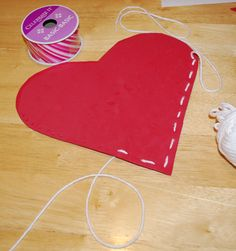 Valentine's Craft: use 2 pieces of construction paper and the kids just use  stickers to decorate (no hot glue gun for me!).   we just use a hole punch to make the holes around the heart (remember to not do the top!) and he can easily push the yarn through the holes.  They make a good place to store all the cards from school and it can hang on a door knob in their room!