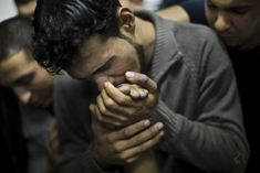 A Palestinian man kisses the hand of a dead relative in the morgue of Al-Shifa Hospital, Palestinian Territories, Gaza City, 2012 - by Bernat Armangué (1978), Spanish