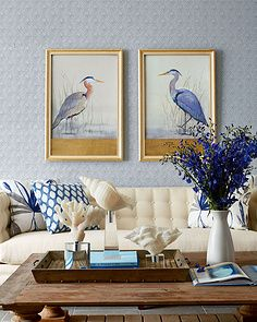 Blue and white living room accented by bird art. Love the mixed print blue pillows and the coral pieces. Both add texture and a feeling of comfort to the space. #livingroomideas