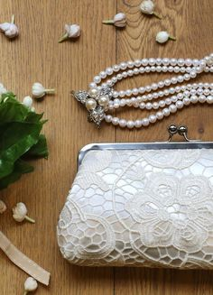 """A classic satin lace clutch in ivory is perfect for both the bride and the bridesmaids. These lace clutches are intentionally sized as travel wallets for passports and boarding passes - perfect for the destination wedding and honeymoon.  """"L'Heritage"""" wedding clutch by ANGEE W."""