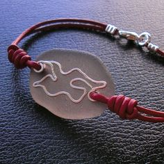 https://flic.kr/p/86qdmF   Seaglass Jewelry - No Limits Seaglass Seagull Bracelet   Inspired by Johnathan seagull soaring against an overcast sky, this sillouette is shaped and hammered from sterling silver wire and backed with an ancient grey seaglass. Straps are red leather cords.