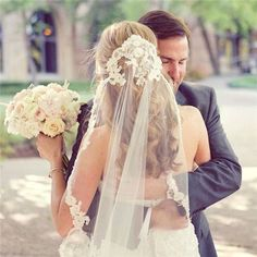Love everything about this photo; the flower bouquet is gorgeous, the veil is stunning, and it captures a beautiful moment between husband and wife