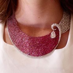 """: """"A wave of pink sapphires and rubies break in to a swirl of Merveille-set diamonds suspending a…"""""""
