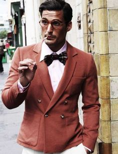 This looks like the '50s. Love the red color of the suit jacket and the bow tie. Nice outfit for men who want to a splash of color to their wardrobe.