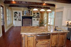 Kitchen open to Keeping Room with Brick fireplace appointed with Beams. By AAA Homes of MS, LLC