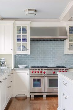 White and blue kitchen features a coffered ceiling with coffers painted light blue dotted with Berling Small Flush Mount lights illuminating white cabinets paired with gray granite countertops and backsplash.