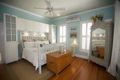 Another view of the aqua and white cottage chic bedroom. Wonderful wall color. (Don't really love the built-in cabinets and row of cupboards surrounding the headboard. Functional vintage pieces would be so much more charming.)