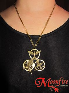 This necklace is the ultimate combination of all three mockingjay designs from The Hunger Games series: The Hunger Games, Catching Fire, and Mockingjay Part The antiqued bronze pendant measures 5 c Hunger Games Fandom, Hunger Games Mockingjay, Katniss And Peeta, Hunger Games Catching Fire, Hunger Games Trilogy, Fandoms, Geeks, Geek Stuff, Bronze Pendant