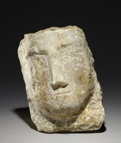 sculpture; Ancient South Arabian; 3rdC BC-3rdC; Yemen; Yemen. Carved calcite-alabaster human head with angular features including nose and mouth but no eyes; very worn and abraded; possibly part of a larger object.