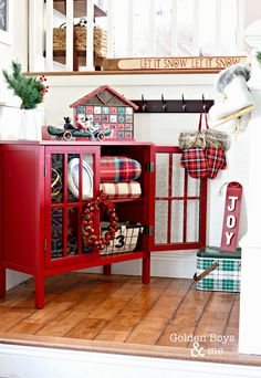 Red bookcase from Target in a rustic Christmas entryway-www.goldenboysandme.com