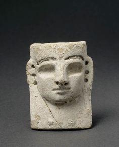 Pendentif en forme de masque de déesse  XIVe - XIIIe siècles avant J.-C.  Minet el Beida, port d'Ougarit, tombe 6 Fritte à glaçure Incrustation de bitume pour figurer les yeux H. : 7,50 cm. ; L. : 6 cm. ; Pr. : 3,40 cm.