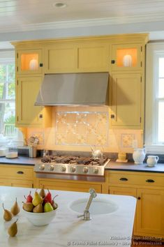 This bright and beautiful country style kitchen by Crown Point Cabinetry features traditional yellow kitchen cabinets and a contrasting wood island. Yellow Kitchen Cabinets, Kitchen Tiles, Kitchen Colors, Kitchen Decor, Kitchen Design, Yellow Kitchens, Dream Kitchens, Updated Kitchen, New Kitchen