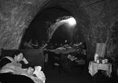 "Hundreds of people, many of whom have lost their homes through bombing, now use the caves in Hastings, a south-east English town as their nightly refuge. Special sections are reserved for games and recreation, and several people have ""set up house"", bringing their own furniture and sleeping on their own beds. Photo taken on December 12, 1940. (AP Photo)"