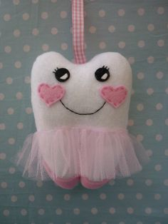 'Loose Tooth?'   Bella Ballerina the Tooth Fairy Pillow will keep your wee ones tooth safe till the tooth fairy arrives.  Hang her from the door or bedhead by the ribbon loop or tuck her under a pillow.   The pocket on the behind is perfect for storing that special lost tooth and keeping money saf...