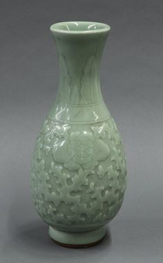 """Chinese Longquan style celadon vase, with stiff leaves to the neck, molded peonies and tendrils to the body, raised on a splayed foot, 14""""h"""