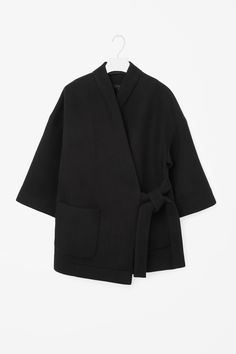 A wrap-over design that is tied at the side of the waist, this coat is made from…