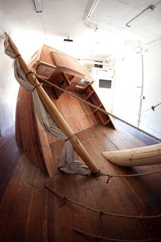 """' To step into Josh Beckman's installation at Machine Project is to enter a world in which anything is possible. All that's required is an active imagination. """"The Sea Nymph"""" does the rest. Made of wood, cloth and rope, """"The Sea Nymph"""" is an approximately life-size model of a sailing ship that Beckman has crammed into the small gallery. Its stern tips steeply skyward. This suggests that the rest of the hull has disappeared through the floor and that the boat is about to sink swiftly. '"""