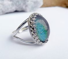 This Mood Ring is created with an aged glass Mood stone that changes colors with your mood/body temperature. The setting is .925 Sterling