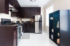 This large kitchen has dark cherry cabinets and stainless steel appliances with a ton of granite countertop space. #bjbproperties #chicagoapartments #rogersparkapartments
