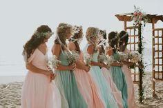 The bridesmaids look like water-nymphs, in their flowing chiffon dresses in shades of peach and aqua. We also love their garlands and simple baby's breath nosegays | Seafoam & Coral Ventura Beach Wedding // Wedgewood Ventura