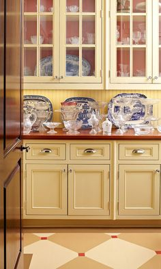 butler's pantry and blue and white dishes are complimented by the warm cabinet color, the wood counter tops and the floor pattern. like!