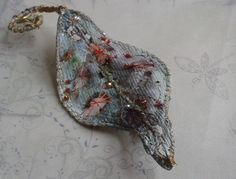 A blue/green leaf created using Tyvek, stitched with metallic threads and embellished with tiny beads by Karen Lane.