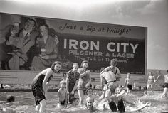 An old photo of people swimming in Pittsburgh below the Iron City sign. #PittsburghSigns #History #TBT