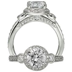 Modern three stone diamond engagement ring featuring a prong set round cut centerstone that is surrounded by micropavé diamonds and bezel set round cut diamond side stones, which are set against a single row micropavé shank.