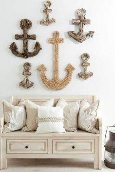 Creative Anchor Gallery Wall... http://www.completely-coastal.com/2016/09/nautical-living-navy-blue-white.html A large rope anchor, surrounded by driftwood anchors make up this fun nautical gallery wall in the entryway.