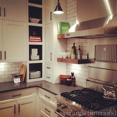 corner treatment, wood floating shelves, subway tile, dark solid surface counters