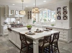 This kitchen island serves double-duty with ample work spaces and formal seating.
