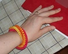 Those who have made lanyards at scout camp will be familiar with the weaving used to make this bracelet.  .  Free tutorial with pictures on how to make a braided ribbon bracelet in 11 steps by jewelrymaking with scissors, thread, and ribbon. How To posted by Jenna Z. Difficulty: Easy. Cost: Cheap.
