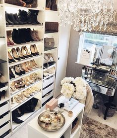 Closet: middle island table, chandilier,  shoe shelf, decor, and fluffy furry rug.