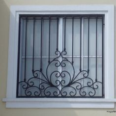 Herrería artística en ventana bien equilibrada mezclando lineas rectas y un diseño creativo . rejas para ventanas