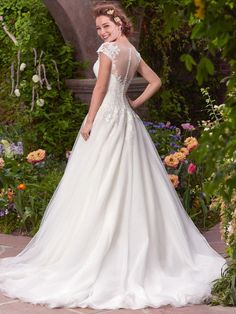 Rebecca Ingram - MAE, Delicate pearl beading and lace appliqués shimmer across the bodice of this tulle ballgown, featuring an illusion bateau neckline and demure cap-sleeves. An illusion back completes the romance of this look. Finished with covered buttons over zipper and inner elastic closure.