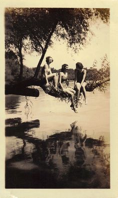 1930's. three young girl friends hanging out swimming in the lake, just another beautiful summer day