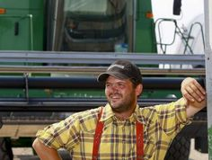 """Wesley Hofer poses in front of a combine on the King Ranch Colony Thursday. Hofer says, he was rushed to the hospital with a staged heart attack in an episode of National Geographic Channel's """"American Colony: Meet the Hutterites""""."""