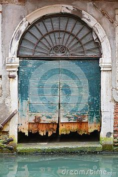 A green huge gate damaged by the Venetian waters in Venice, Italy, Europe.