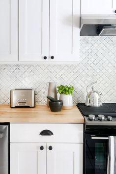 white kitchen-paint, butcher block counter, new hardware good lower cost updates, like the diagonal tile pattern backsplash