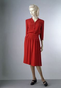 A day dress is from the Utility Collection by the Incorporated Society of London Fashion Designers for the Board of Trade. V&A 1942.