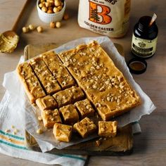 Squares of tablet on baking parchment topped with crushed hazelnuts