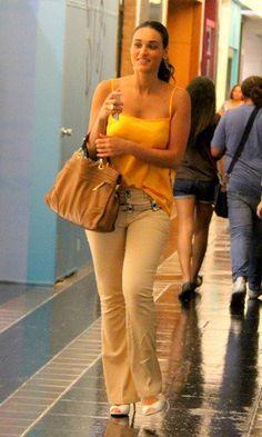 Para um passeio no shopping, a atriz Débora Nascimento optou por um look mais casual. A calça jeans flare na cor amarelo claro complementa a blusa de cetim laranja. Nos pés, o salto branco dá sofisticação ao visual que tem como acessório a bolsa marrom.