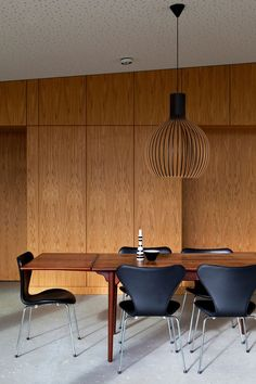 Hans J. Wegner dining table in teak, Arne Jacobsen´s Seven chairs in leather and Secto pendant light by Seppo Koho. Interior from Villa Aarhus by Friis & Moltke. / ArchDaily