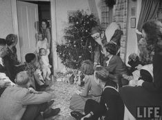 Vintage Christmas Photograph ~ Fred Andrews dressed as Santa Claus distributing presents to younger members of the James Ferdinand Irwin family ~ Neosho Rapids, KS 1945. From kcmeesha.com.