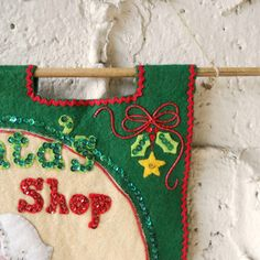 This sweet vintage holiday banner is a painstakingly handmade piece of holiday folk art featuring a green and cream acrylic felt background and Santa