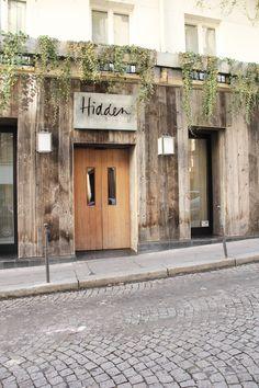 'Hidden' shop front with dropping foliage and a faded wooden face. Facade Design, Exterior Design, Architecture Design, Merci Paris, Shop Facade, Exterior Signage, Cafe Interior Design, Interior Paint, Cafe Shop
