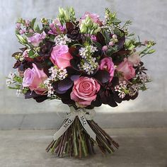 You can't improve upon a rose, but we've given stunning pink roses a contemporary and timeless McQueens twist, studded with delicate flowers and contrasting seasonal greenery.