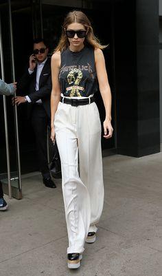 Gigi Hadid veste regata podrinha com pegada rock, calça pantalona off white, arrematando com cinto preto e flatforms