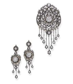 AN ANTIQUE DIAMOND BROOCH AND EAR PENDANTS. The old-cut diamond cluster within a two-row diamond collet surround with black enamel detail to the scroll top and suspending a knife-edge and diamond fringe, matching ear pendants en suite, mounted in silver and gold, circa 1880, 8.0 cm. long, 5.3 cm. long